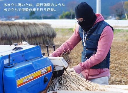 銀行強盗のような出で立ちで脱穀作業を行う店長。