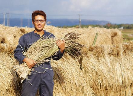 緑米をかかえてニヤリと笑う店長。