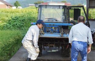 トラクターを修理する井芹さんと北野さん。