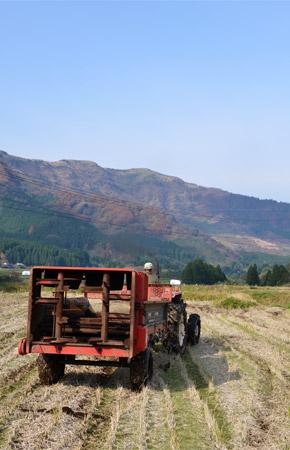 阿蘇の山々をバックに堆肥を散布するトラクター
