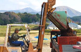フォークリフトを使い、トラクターに堆肥を積んでいく。