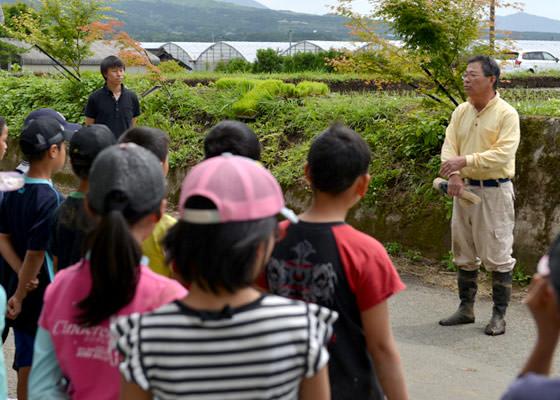 田植え終了後、生徒たちにねぎらいに言葉をかける井芹政重さん。今年から有機堆肥の使用も止め、自然栽培での米作りに移行した。