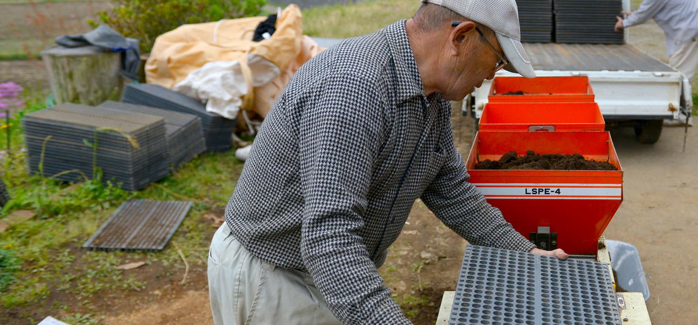 種まきをする酒井さん。