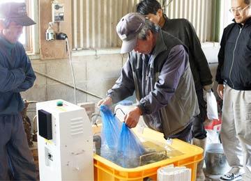 喜多無農薬米生産会が籾の消毒をやっていたので、ついでにやってもらった。籾を浸しているのは長野訓之さん、左に立っているのは北野鉄矢さん。