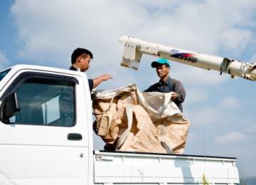 収穫した籾は専用の袋に入れられ、トラックでライスセンターに運ばれる。左は笠野さんの息子さん、右は宇都宮さん。
