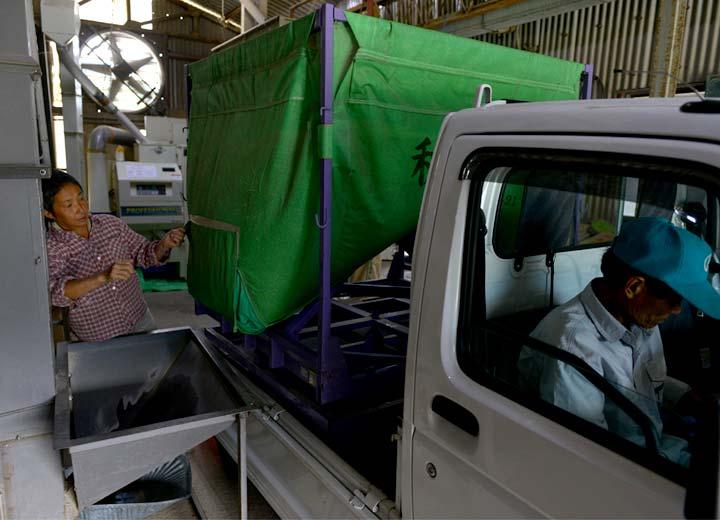 この日は高島和子さんが乾燥機の担当。到着した藤原さんの籾を乾燥機へ入れる手伝いをする。