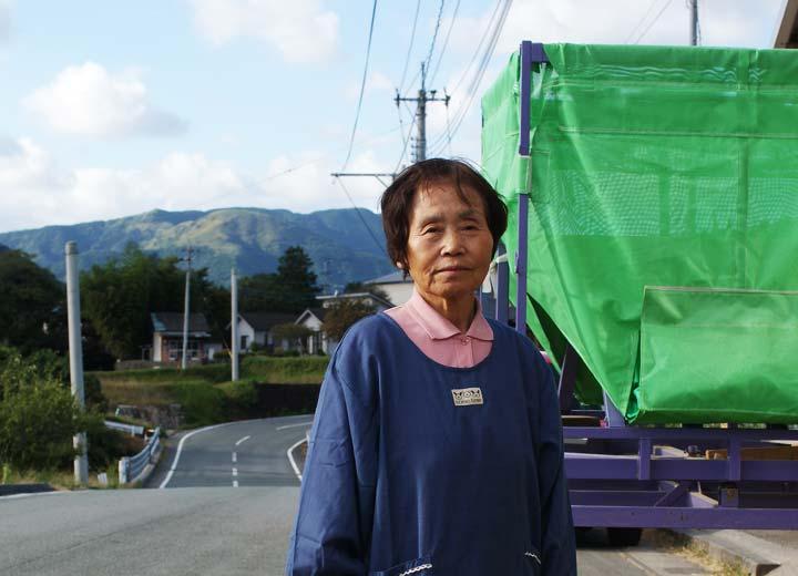 生産者の後藤松子さん。撮影場所は喜多のライスセンターの前。後ろある緑色の袋は籾の運搬機。